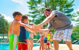 Director Ian high fiving campers by pool