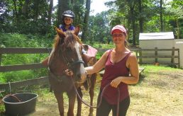 Staff helping camper at horseback riding