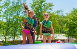 Two girls jumping on water trampoline