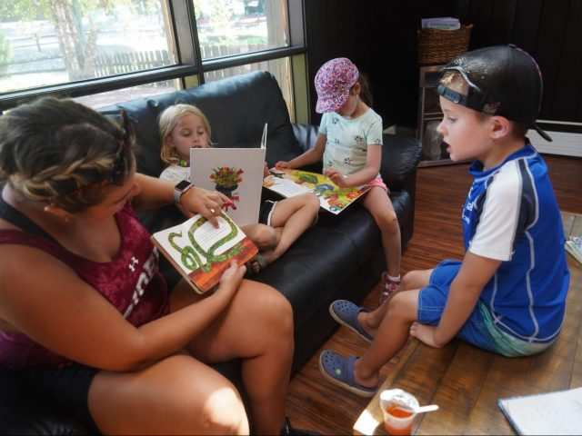 An adult reading to children in the library