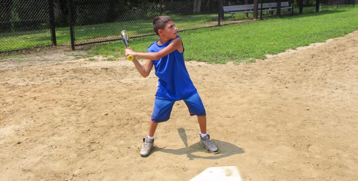 Camper hitting a baseball bat
