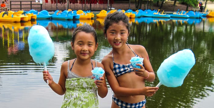 Two girls holding cotton candy by lake