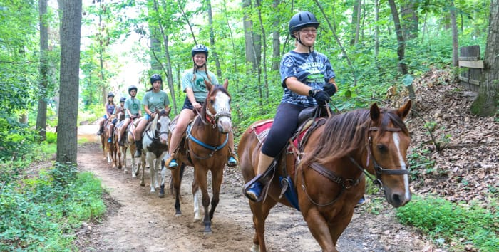 Campers horseback riding through woods