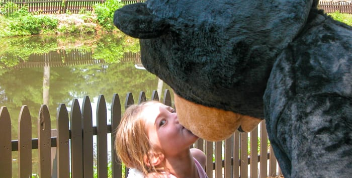 Girl kissing the mascot bear