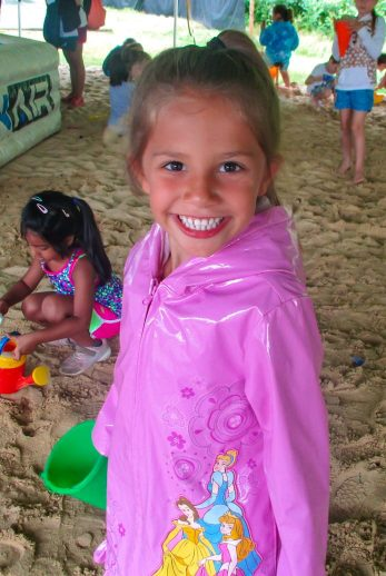 Girl playing in sand with pink raincoat