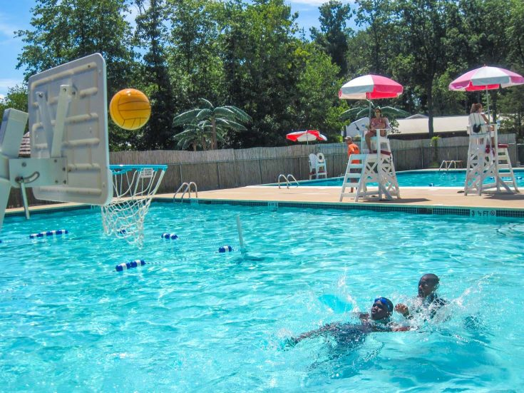 Two campers playing pool basketball
