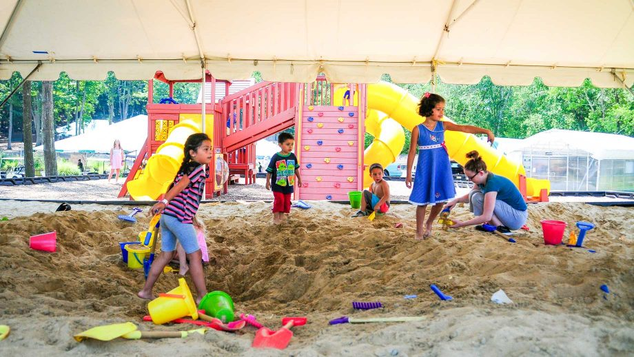 Kids playing in sand pit by playground
