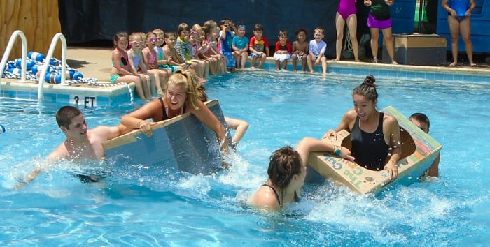 Staff in cardboard boats in pool