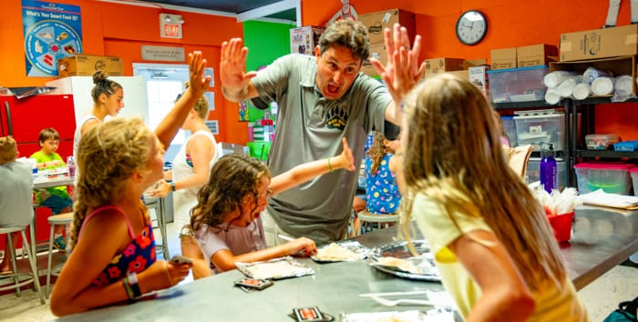 Director giving high fives to kids at arts and crafts