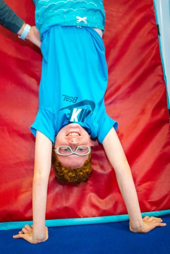 Boy upside down on gymnastics equipment