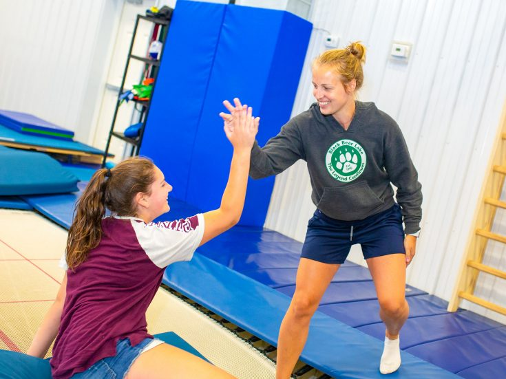 Gymnastics staff helping a girl