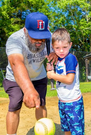 Boy learning to hit baseball with staff's help
