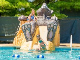 Kids on giant bear by pool
