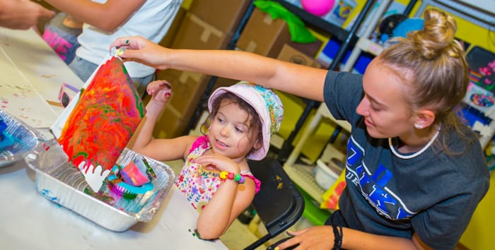 Staff helping a young camper at arts and crafts