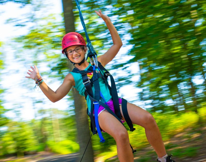 Girl zip lining without using her hands